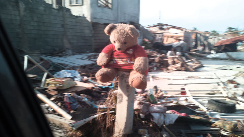 PRESENT TENSE. Gift-giving has taken new meaning in these calamitous times. One can't help but think twice about how to spend money, even for presents for loved ones. No doubt that trinkets, gadgets and toys, like this stuffed bear propped eerily on a post somewhere in a typhoon-ravaged town up north, can make people happy. But how useful — and essential — are they in the long run? (Foto by Freon L. Ollival)