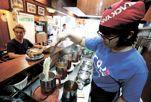 "SOUTH KOREANS DEFEND DIET. A cook prepares ""ramyeon"" instant noodles for a customer at a ramyeon restaurant in Seoul, South Korea. A study by a United States hospital that found excessive consumption of instant noodles was associated with health risks has left a bad taste in the mouth among South Koreans. (AP FOTO)"