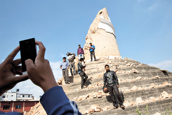EARTHQUAKE TOURISM. Locals take snapshots with their cell phones at the historic Dharahara Tower, a city landmark, that was damaged in last week's earthquake in Kathmandu, Nepal. (AP FOTO)