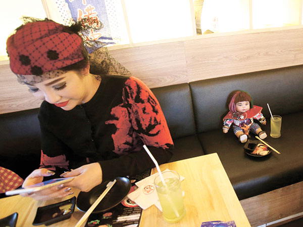"""FAD THAI DOLLS. Supavadee Tapmalai uses her smartphone next to a """"child angel"""" doll at a Japanese restaurant in Bangkok, Thailand. The dolls, which are said to bring good luck to their owners, became a media sensation last week after a leaked memo from a Thai budget airline gave pointers on how they could be treated like passengers if they have a paid-for seat. (AP PHOTO)"""