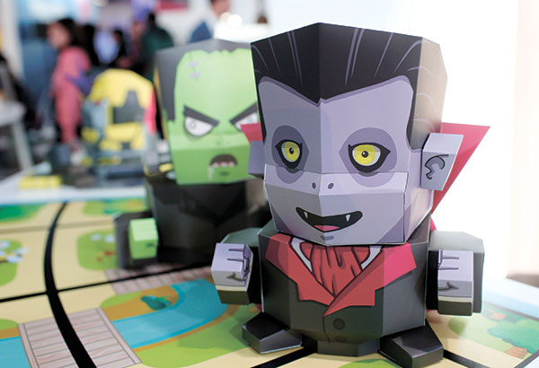 "PROGRAMMED SKINS. Interactive paper toys fitted onto a robot that is controlled by an app to help children learn programming are displayed during last week's Mobile World Congress wireless show in Barcelona, Spain. Aimed at children as young as eight years old, the Kamibot robot can be covered with paper-made ""skins"" to turn it into a variety of characters, including Dracula, Frankenstein, and several popular figures in Korea. (AP PHOTO)"