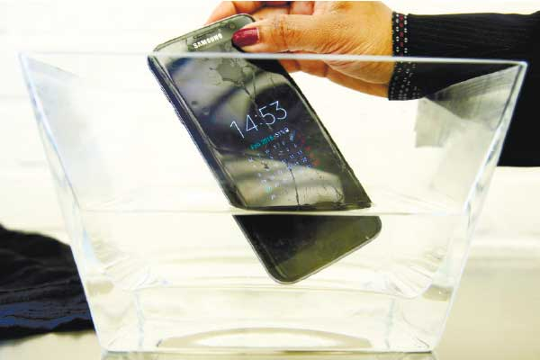 """DUNK TEST. A waterproof Samsung Galaxy S7 Edge mobile phone is submersed in water during a preview of Samsung's flagship store, Samsung 837, in New York's Meatpacking District. SquareTrade, a company that offers extended-protection plans for gadgets, said the Galaxy S7 and S7 Edge still functioned after being submerged in water for 30 minutes. Audio was """"permanently muffled and distorted"""" after the dunking, but the Samsung phones still outlasted Apple's iPhones in SquareTrade's water tests. (AP PHOTO)"""