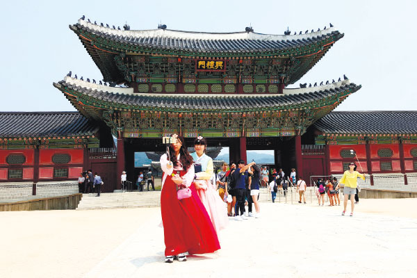 Girls in traditional Hanbok costumes take selfies at the Gyeongbokgung Palace