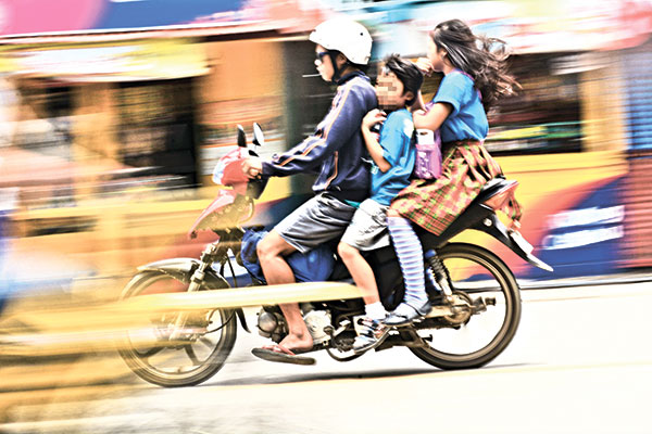 "RISKY RIDE. Children without helmets riding a motorcycle, a clear violation of Republic Act. 10666, or the ""Children's Safety on Motorcycles Act of 2015."" (SUN.STAR FILE)"